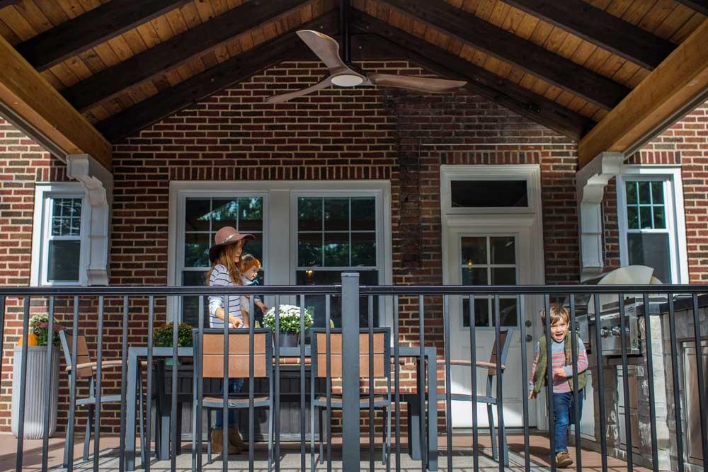Covered Deck Wood Ceiling Black Railing Brick House